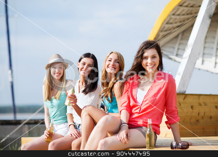 girls with drinks on the beach stock photo, summer holidays and vacation - girls with drinks on the beach by Syda Productions