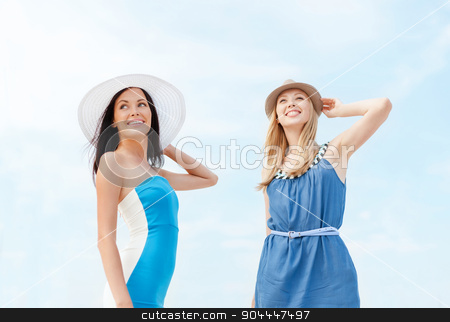 girls in dresses with hats on the beach stock photo, summer holidays and vacation concept - girls in dresses with hats on the beach by Syda Productions
