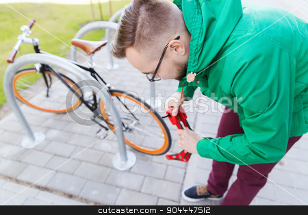 hipster man fastening fixed gear bike with lock stock photo, people, security, safety and lifestyle - young hipster man fastening fixed gear bike with blocking lock on city street parking by Syda Productions