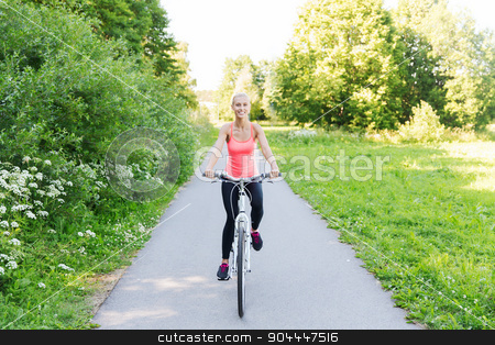 happy young woman riding bicycle outdoors stock photo, fitness, sport, people and healthy lifestyle concept - happy young woman riding bicycle outdoors by Syda Productions