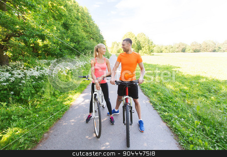 happy couple riding bicycle outdoors stock photo, fitness, sport, people and healthy lifestyle concept - happy couple riding bicycle outdoors at summer by Syda Productions