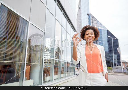 happy young african american businesswoman in city stock photo, business, gesture and people concept - young smiling african american businesswoman in city showing ok hand sign by Syda Productions