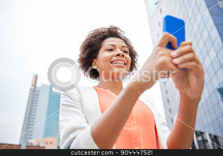 happy african businesswoman with smartphone stock photo, business, technology, communication and people concept - young smiling african american businesswoman with smartphone in city by Syda Productions