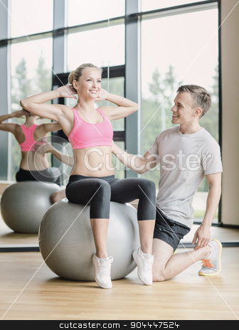 smiling man and woman with exercise ball in gym stock photo, sport, fitness, lifestyle and people concept - smiling man and woman with exercise ball in gym by Syda Productions