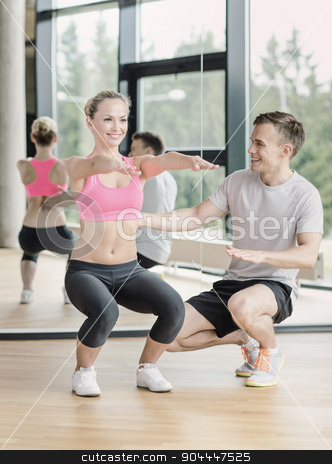 smiling woman with male trainer exercising in gym stock photo, sport, fitness, lifestyle and people concept - smiling woman with male personal trainer exercising in gym by Syda Productions