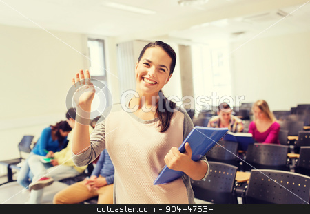 group of smiling students in lecture hall stock photo, education, high school, gesture, teamwork and people concept - group of smiling students with notepads waving hand in lecture hall by Syda Productions