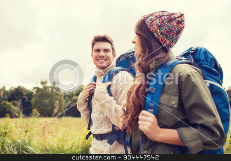 smiling couple with backpacks hiking stock photo, adventure, travel, tourism, hike and people concept - smiling couple walking with backpacks outdoors by Syda Productions