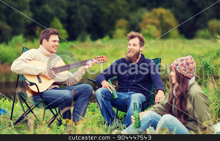 group of tourists playing guitar in camping stock photo, adventure, travel, tourism and people concept - group of smiling tourists playing guitar and drinking beer in camping by Syda Productions