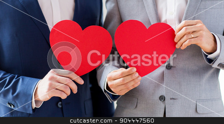 close up of male gay couple holding red hearts stock photo, people, homosexuality, same-sex marriage, valentines day and love concept - close up of happy married male gay couple holding red paper heart shapes on wedding by Syda Productions