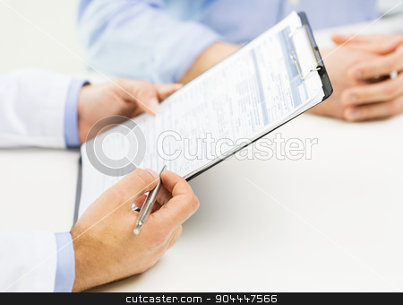 close up of male doctor and patient with clipboard stock photo, medicine, health care, people and prostate cancer concept - close up of f male doctor and patient hands with clipboard by Syda Productions