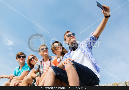 happy friends with smartphone taking selfie stock photo, friendship, leisure, summer, technology and people concept - group of happy friends with smartphone taking selfie outdoors by Syda Productions