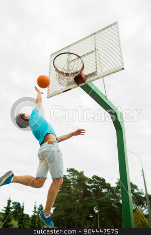 young man playing basketball outdoors stock photo, sport, game and basketball concept - young man throwing ball into basket outdoors by Syda Productions