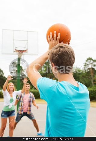 group of happy teenagers playing basketball stock photo, summer vacation, sport, games and friendship concept - group of happy teenagers playing basketball outdoors from back by Syda Productions