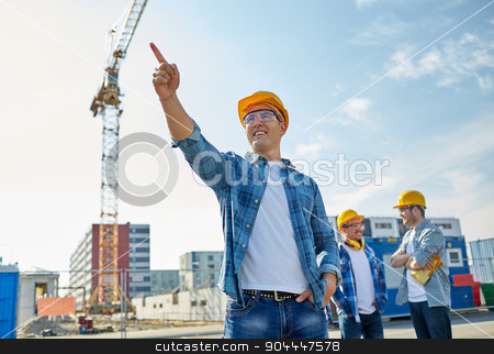 builders pointing finger aside on construction stock photo, business, building, teamwork and people concept - group of smiling builders in hardhats pointing finger aside on construction site by Syda Productions