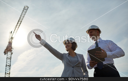happy builders in hardhats with tablet pc outdoors stock photo, business, building, teamwork, technology and people concept - smiling man and woman in hardhats with tablet pc computer pointing finger up at construction site by Syda Productions