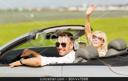happy man and woman driving in cabriolet car stock photo, transport, road trip, leisure, gesture and people concept - happy man and woman driving in cabriolet car and waving hand by Syda Productions