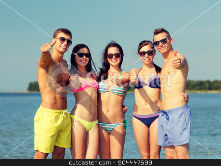smiling friends in sunglasses on summer beach stock photo, friendship, sea, holidays, gesture and people concept - group of smiling friends wearing swimwear and sunglasses showing thumbs up on beach by Syda Productions