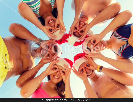 smiling friends in circle on summer beach stock photo, friendship, christmas, summer vacation, holidays and people concept - group of smiling friends wearing swimwear and santa helper hats standing and having fun in circle over blue sky by Syda Productions