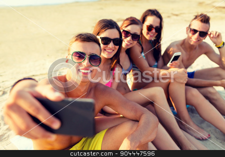 friends with smartphones on beach stock photo, friendship, leisure, summer, technology and people concept - friends sitting and taking selfie with smartphone on beach by Syda Productions