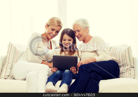 smiling family with tablet pc at home stock photo, family, generation, technology and people concept - smiling mother, daughter and grandmother with tablet pc computer sitting on couch at home by Syda Productions