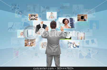 businessman working with virtual screen stock photo, business, people, communication, technology and connection concept - businessman working with images on virtual screen over blue background from back by Syda Productions