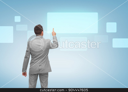 businessman pointing finger to virtual screen stock photo, business, people, advertisement and technology concept - businessman pointing finger or touching blank virtual screen over blue background from back by Syda Productions