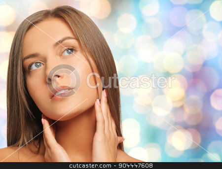 beautiful young woman touching her neck stock photo, beauty, people and health concept - beautiful young woman touching her neck over blue holidays lights background by Syda Productions