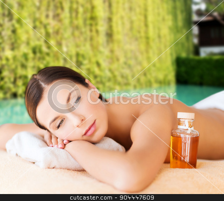 happy woman in beauty spa stock photo, spa, beauty, people and body care concept - happy woman lying on the massage desk with oil bottle over green natural background by Syda Productions