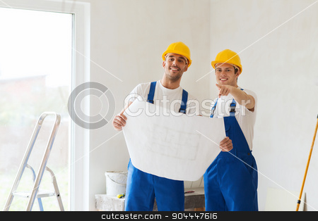 group of builders with blueprint stock photo, building, teamwork and people concept - group of smiling builders in hardhats with blueprint indoors by Syda Productions