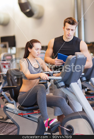 woman with trainer on exercise bike in gym stock photo, sport, fitness, lifestyle, technology and people concept - woman with trainer working out on exercise bike in gym by Syda Productions