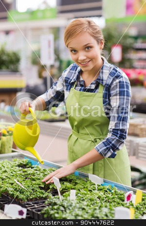 happy woman with watering can in greenhouse stock photo, people, gardening and profession concept - happy woman or gardener with watering can and seedling in greenhouse by Syda Productions