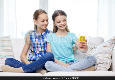 happy girls with smartphone taking selfie at home stock photo, people, children, technology, friends and friendship concept - happy little girls sitting on sofa and taking selfie with smartphone at home by Syda Productions