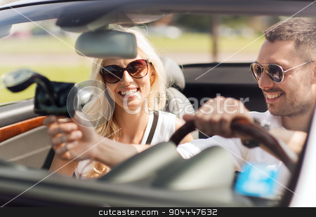 happy couple usin gps navigation system in car stock photo, road trip, leisure, travel, technology and people concept - happy man and woman driving car and using gps navigation system by Syda Productions