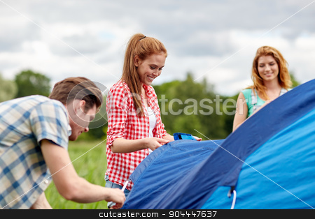 group of smiling friends setting up tent outdoors stock photo, camping, travel, tourism, hike and people concept - group of smiling friends setting up tent outdoors by Syda Productions