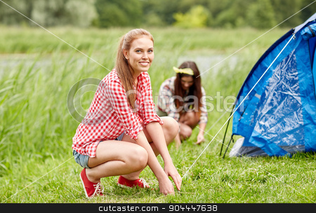 smiling friends setting up tent outdoors stock photo, camping, travel, tourism, hike and people concept - smiling friends setting up tent outdoors by Syda Productions