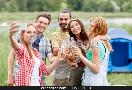 happy friends taking selfie by smartphone at camp stock photo, camping, travel, tourism, hike and people concept - happy friends with glass bottles drinking cider or beer and taking selfie by smartphone at camping by Syda Productions