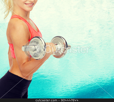 close up of sporty woman with heavy steel dumbbell stock photo, fitness, healthcare and exercise concept - close up of young sporty woman with heavy steel dumbbell by Syda Productions