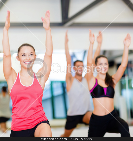 group of smiling people exercising in the gym stock photo, fitness, sport, training, gym and lifestyle concept - group of smiling people exercising in the gym by Syda Productions
