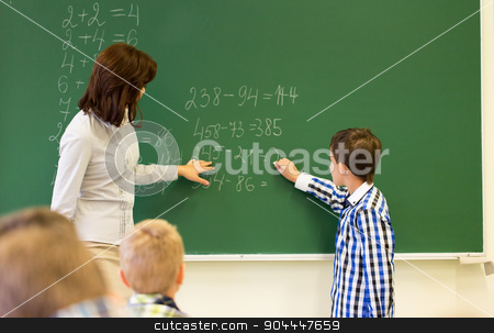schoolboy with math teacher writing on chalk board stock photo, education, elementary school, learning, math and people concept - close up of little schoolboy with teacher writing on chalk board and solving task in classroom by Syda Productions
