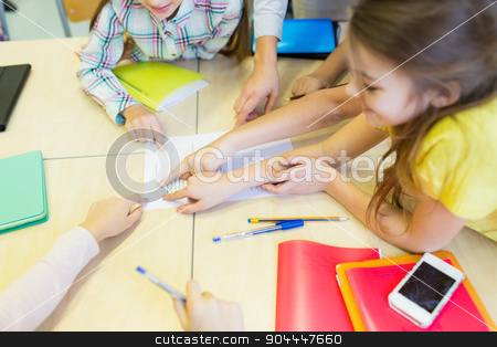 group of school kids pointing fingers to test stock photo, education, elementary school, learning and people concept - close up of school kids pointing fingers to paper with test on desk at classroom by Syda Productions
