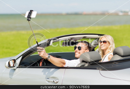 happy couple in car taking selfie with smartphone stock photo, road trip, leisure, couple, technology and people concept - happy man and woman driving in cabriolet car and taking picture with smartphone on selfie stick by Syda Productions