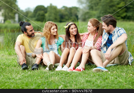 group of smiling friends talking outdoors stock photo, friendship, leisure, summer and people concept - group of smiling friends sitting on grass and talking outdoors by Syda Productions