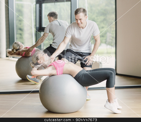 smiling young woman with personal trainer in gym stock photo, fitness, sport, exercising and diet concept - smiling young woman and personal trainer in gym by Syda Productions