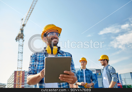 builder in hardhat with tablet pc at construction stock photo, business, building, industry, technology and people concept - smiling builder in hardhat with tablet pc computer over group of builders at construction site by Syda Productions