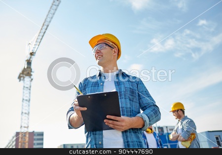 builder in hardhat with clipboard at construction stock photo, business, building, paperwork and people concept - happy builder in hardhat with clipboard and pencil over group of builders at construction site by Syda Productions