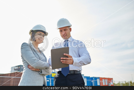 happy builders in hardhats with tablet pc outdoors stock photo, business, building, teamwork, technology and people concept - smiling man and woman in hardhats with tablet pc computer at construction site by Syda Productions