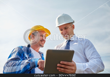 happy builders in hardhats with tablet pc outdoors stock photo, business, building, teamwork, technology and people concept - smiling builders in hardhats with tablet pc computer outdoors by Syda Productions