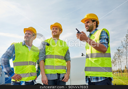 happy male builders in vests with walkie talkie stock photo, industry, building, technology and people concept - happy male builders in high visible vests with walkie talkie or radio outdoors by Syda Productions