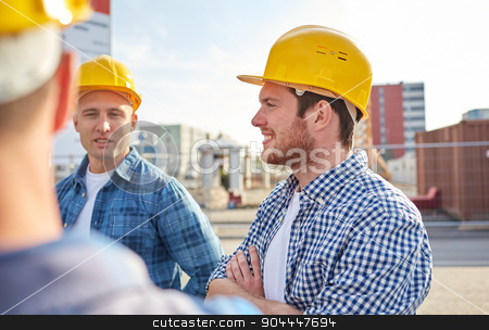 group of smiling builders in hardhats outdoors stock photo, business, building, teamwork and people concept - group of smiling builders in hardhats at construction site by Syda Productions