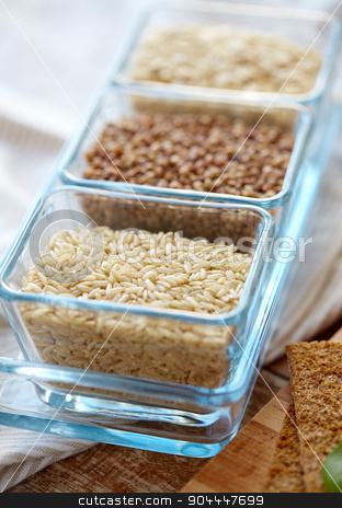 close up of grain in glass bowls on wooden table stock photo, food, agriculture, cereals and healthy eating concept - close up of buckwheat, oatmeal and rice grain on wooden table by Syda Productions